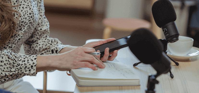 Manos de mujer sosteniendo un móvil apoyándose en una libreta situada frente a dos micrófonos